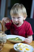 young child eating spinach - stock photo
