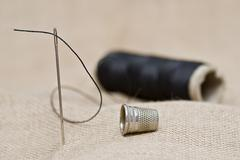 thimble and needle. - stock photo