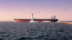 Cargo ship passing by lighthouse at the sea port Stock Footage