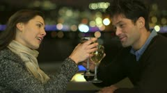 Couple drinking wine raise their glasses for a toast Stock Footage