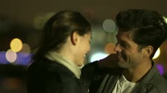 A couple in love enjoy an intimate moment against the backdrop of city lights  - stock footage