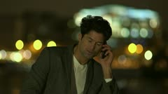 Attractive man speaking on the telephone outdoors, in the city at night Stock Footage