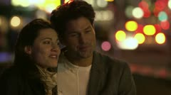 A happy couple in an embrace spend time together talking in the city at night Stock Footage