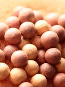 Beige cosmetics multicolor rouge balls background, macro view Stock Photos