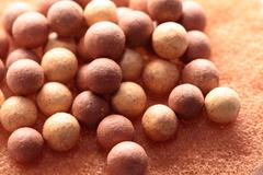 Stock Photo of beige cosmetics multicolor rouge balls background, macro view