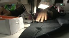 Textile Garment Factory Workers: CU hands feed fabric into sewing machine POV - stock footage