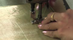 Stock Video Footage of Textile Garment Factory Workers: CU female hands sewing a piece at machine