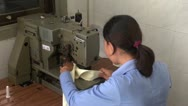Textile Garment Factory Workers: Over shoulder worker at heavy sewing machine Stock Footage