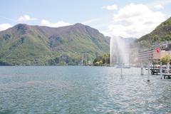 mountainside villas and appartments at lake with waterfountain in the city of - stock photo