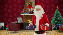 Santa Claus weighting presents in his modern Christmas Office Stock Footage