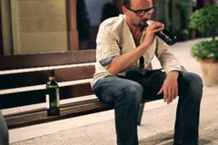 Drunk man with bottle of vine sitting on bench in the evening Stock Footage
