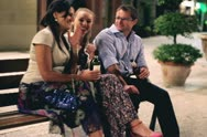 Happy people drinking alcohol on bench in the evening, steadycam shot Stock Footage