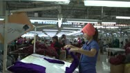 Textile Garment Factory Workers: MS worker folds purple cut pieces Stock Footage