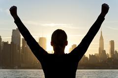 Nainen juhlii kädet ylhäällä auringonnousun New Yorkissa Kuvituskuvat