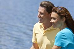 Happy man and woman couple sitting outside by water Stock Photos
