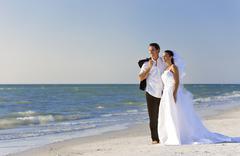 Bride & groom man woman married couple at beach wedding Stock Photos