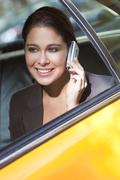 young woman talking on cell phone in yellow taxi - stock photo