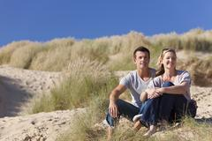 Romantic man and woman couple sitting together on a beach Stock Photos