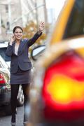 young woman on cell phone hailing a yellow taxi cab - stock photo