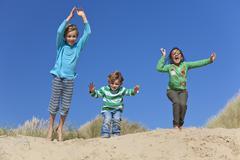 Three children arms raised jumping having fun on beach Stock Photos