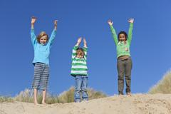 Three children arms raised having fun on beach Stock Photos