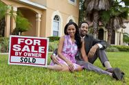 Happy african american couple beside house for sale sold sign Stock Photos