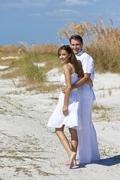 romantic man and woman couple walking on an empty beach - stock photo