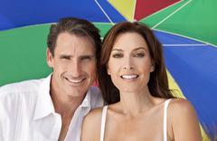 Man & woman couple under multi colored umbrella on beach Stock Photos