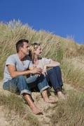 Romantic man and woman couple sitting together on beach Stock Photos