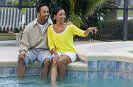 Happy african american couple sitting by swimming pool pointing Stock Photos