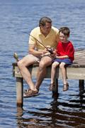 Father fishing with his son on a jetty in summer Stock Photos