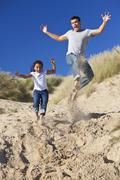 man & girl, happy father and daughter jumping at beach - stock photo