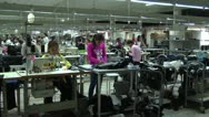 Textile Garment Factory Workers: WS pan interior factory with purple worker FG Stock Footage