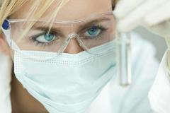 female scientist or woman doctor analyzing test tube in laboratory - stock photo