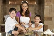 Stock Photo of mother, son & daughter family in kitchen cooking & baking