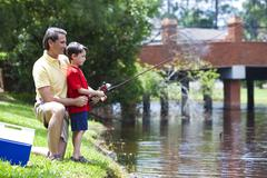 father fishing with his son on a river - stock photo