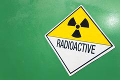 Radioactive warning sign on a green container Stock Photos