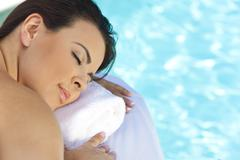 beautiful young woman relaxing by pool at health spa - stock photo