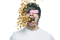3d technology conceptual photo of young man in stereo glasses eating popcorn Stock Photos
