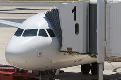 airplane at an airport with passenger gangway in position - stock photo