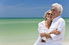 happy senior couple looking to sea on a tropical beach - stock photo
