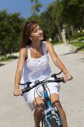 Beautiful woman cycling in white sun dress Stock Photos