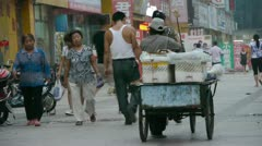Traders seller pushing a tricycle in street,on Urban town road,China Chinese pe Stock Footage