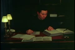 Priest in Venice, Italy, at his desk writing sermon, wide shot Stock Footage