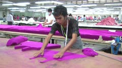 Textile Garment Factory Workers: CU worker preps purple garment pieces Stock Footage