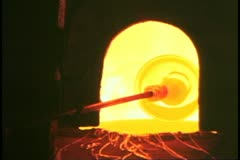 Island of Murano, Italy, glassblowers at work, turning piece in furnace Stock Footage