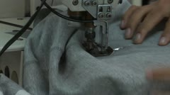 Textile Garment Factory Workers: CU worker hand push fabric in sewing machine Stock Footage