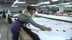 Textile Garment Factory Workers: WS worker prepares large pattern for cutting Stock Footage