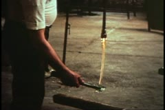 Island of Murano, Italy, glassblowers at work, stretching long length of glass Stock Footage