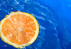 Orange in blue water Stock Photos